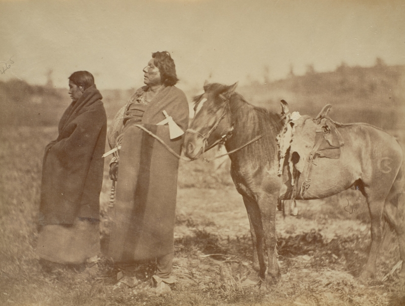 Chief Gre-Othe-Nuzhe (Standing Hawk), Omaha, and wife Mi-Honga with saddled horse